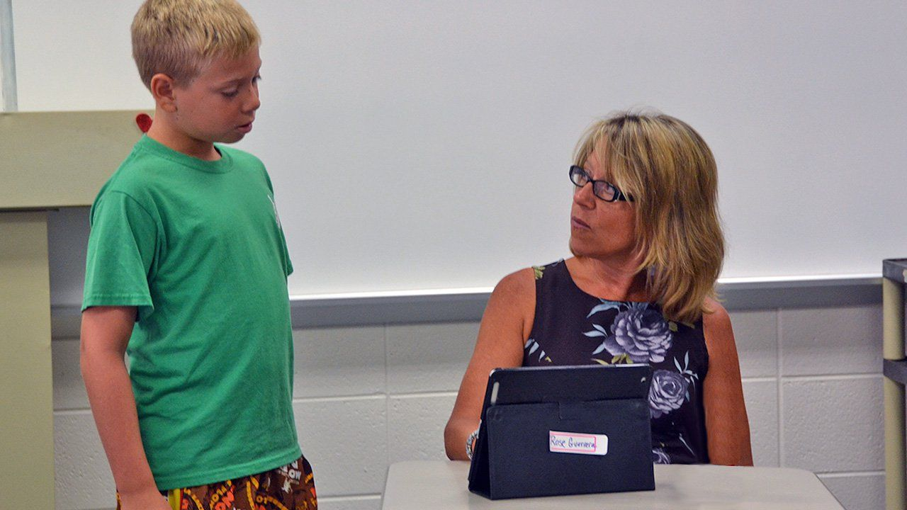 A female teacher in glasses is sitting at a desk with a tablet in front of her looking up towards a young boy. The young boy is wearing a green shirt and is standing to her left.