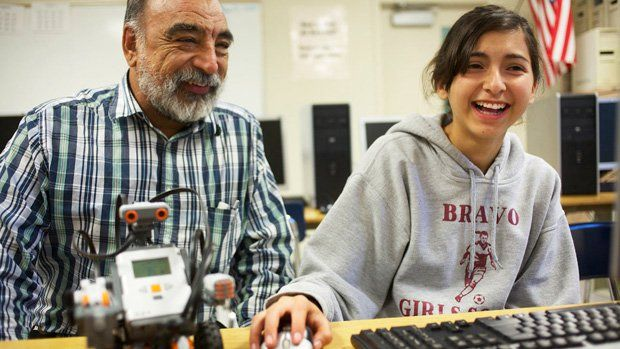 Teacher and student at the computer with her robot