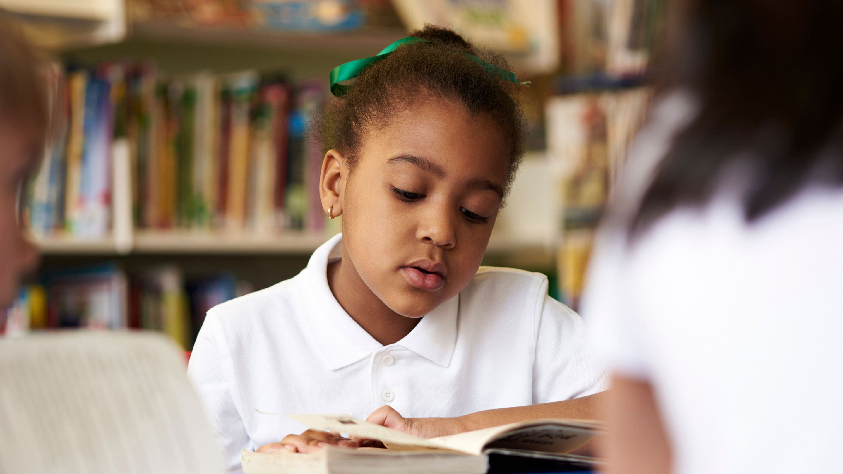photograph of a young girl reading a book