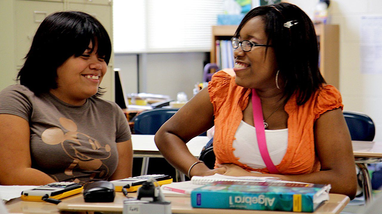 Two girls smiling, sitting at a desk