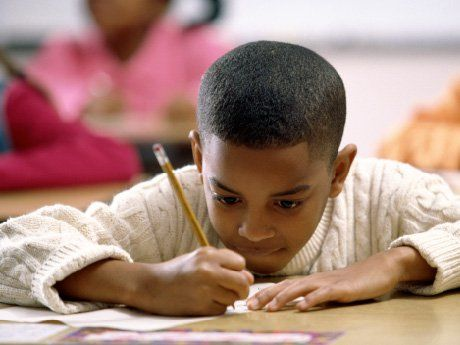 Boy in deep concentration writing with pencil
