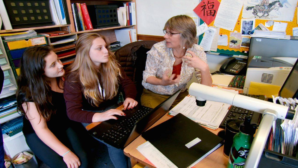 two high school aged students working with a teacher around a computer