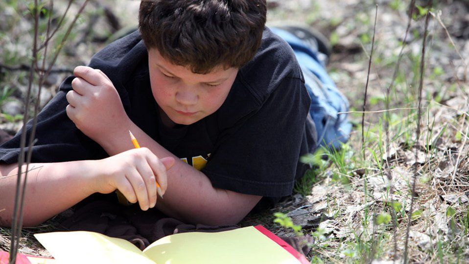 A young boy is lying in the grass with a pencil in his hand, looking down at a red notebook filled with yellow paper