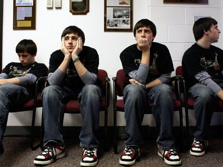 The same teenage boy is seen sitting in four different chairs, next to each other, waiting in a school building.