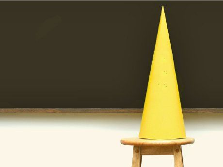 Yellow dunce cap sitting on a stool in front of a blackboard