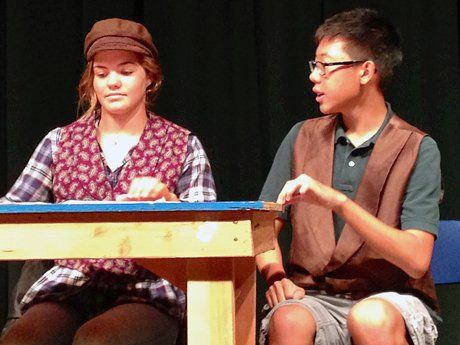 Girl wearing a cap and a boy sitting at a table on stage
