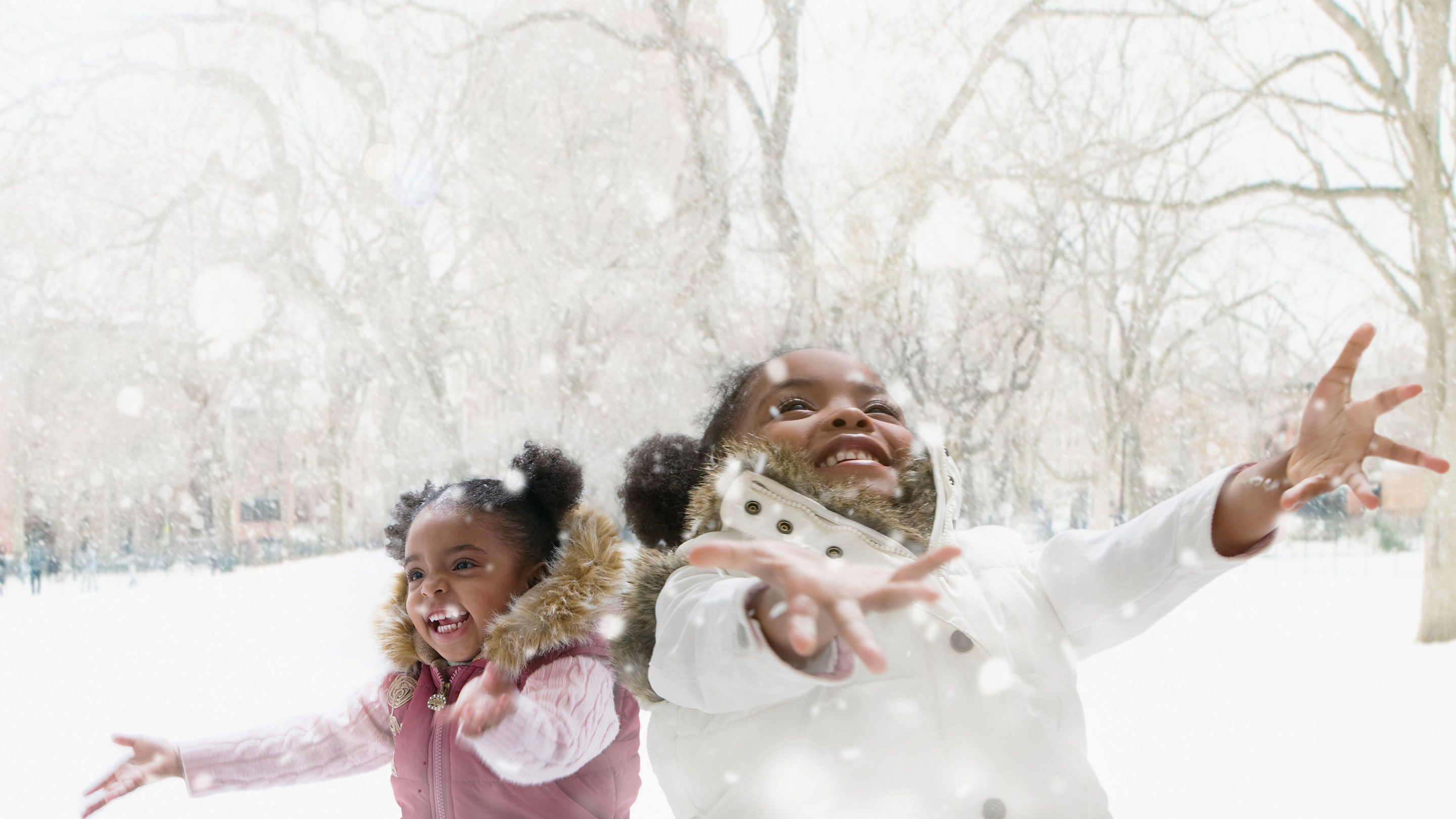 photograph of two students playing in the snow