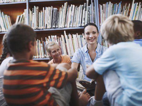 Elementary school children sitting on the floor listening to their teacher