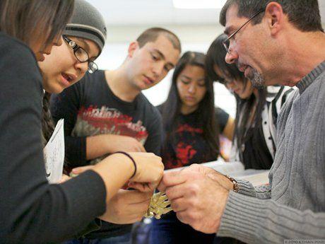 Students gathered around teacher in conversation looking at bones