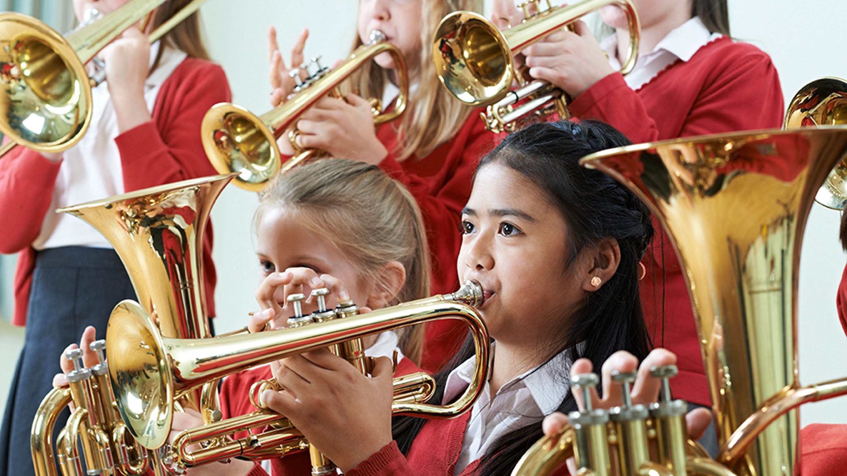 Six young girls in uniform -- a blue skirt, white button up shirt, and a red blouse -- are all playing either the tuba or trumpet.