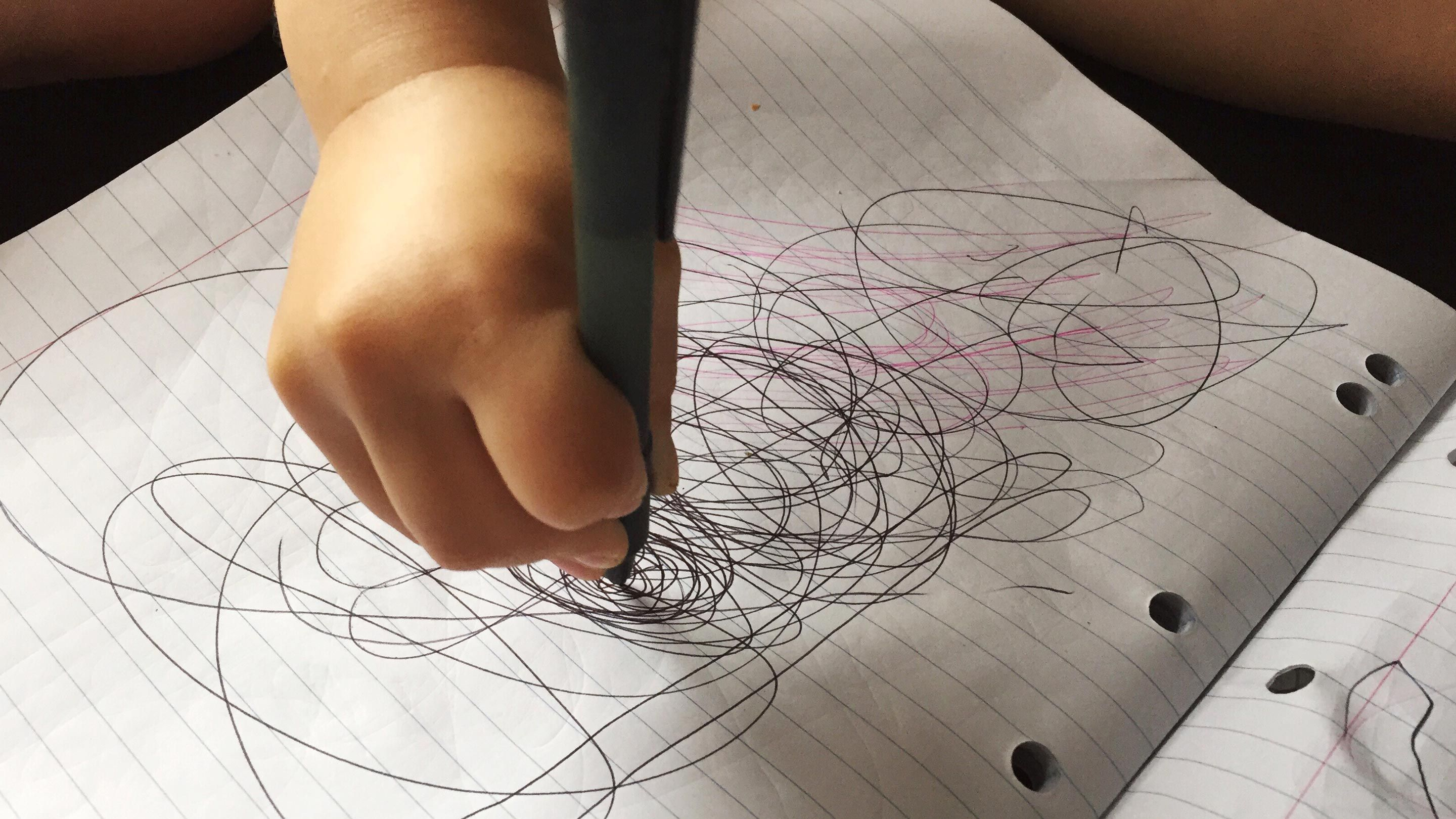 A child's hand scribbling in pen in a lined notebook