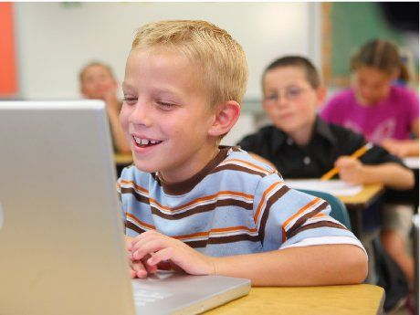 Boy at his desk laughing at something on his laptop