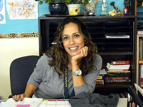 Smiling woman sitting at her teacher's desk