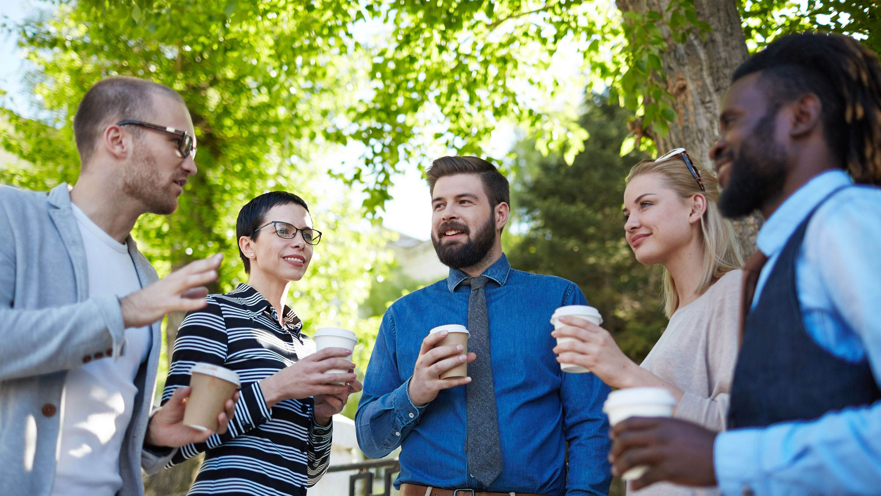 A group of teachers chat over coffee.