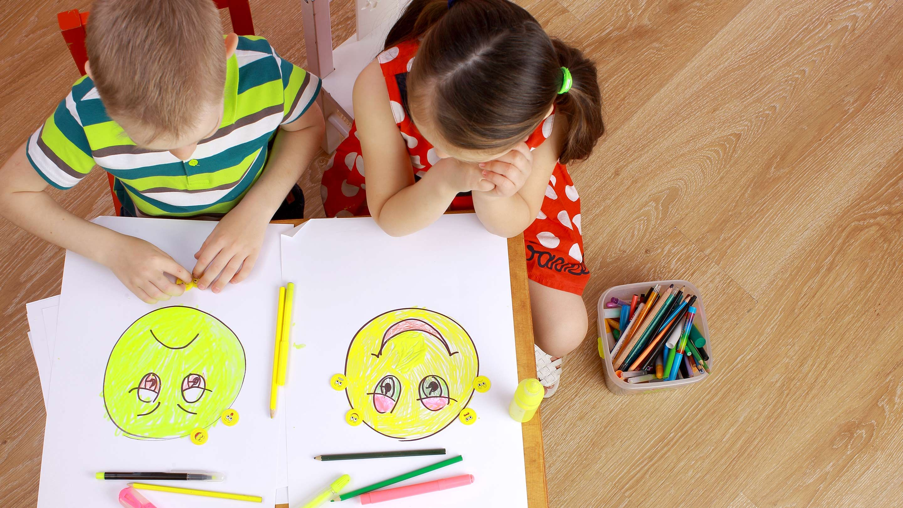 Two small children place facial expression stickers on drawings of a happy face and sad face.