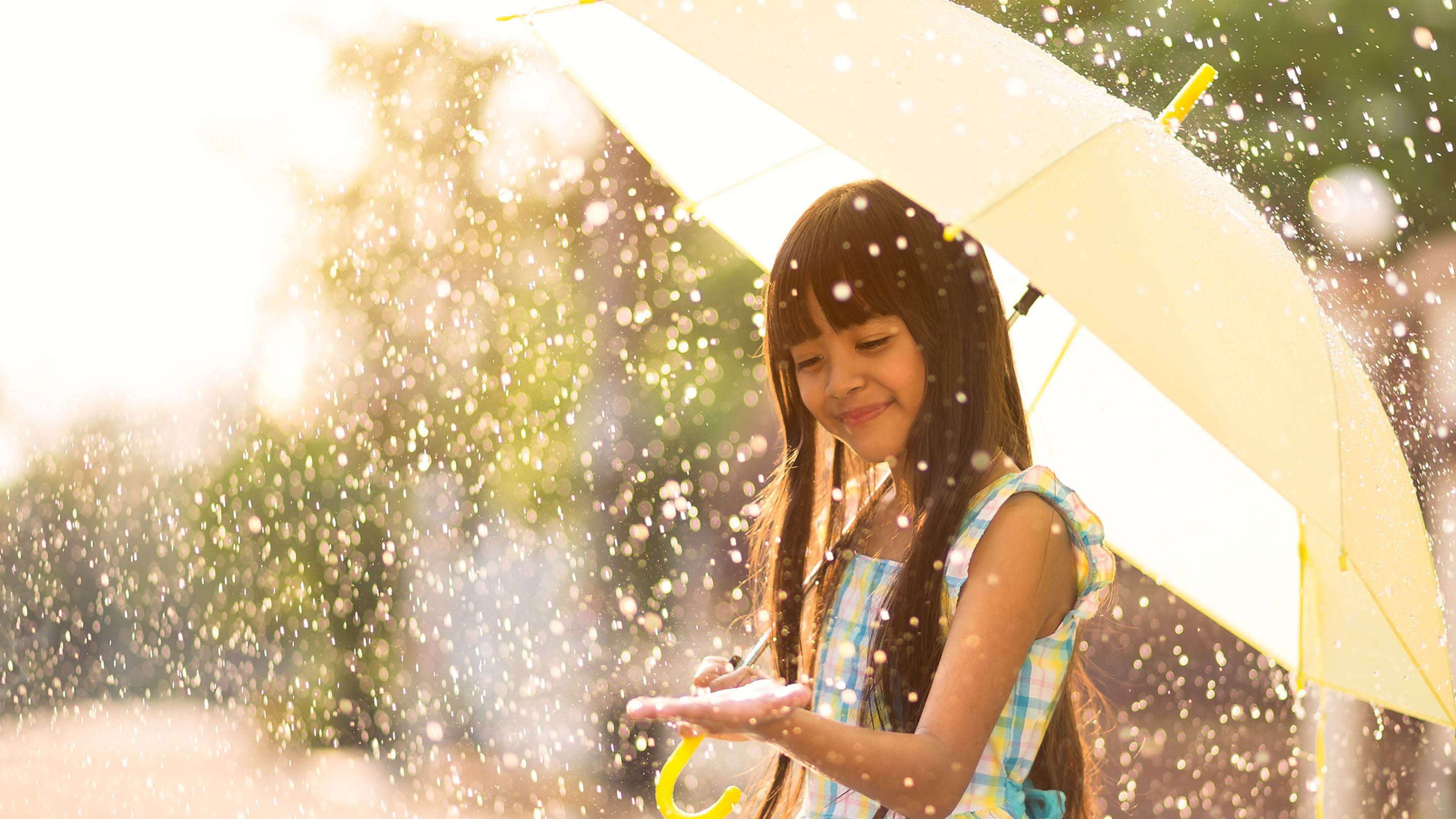 Young girl smiling and holding an umbrella, with hand extended touching raindrops.