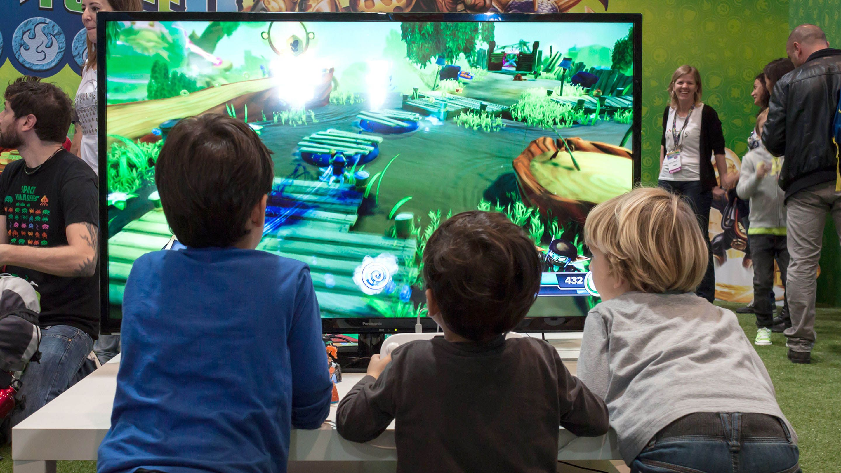 Facing a large monitor, three elementary school-aged boys play a video game.