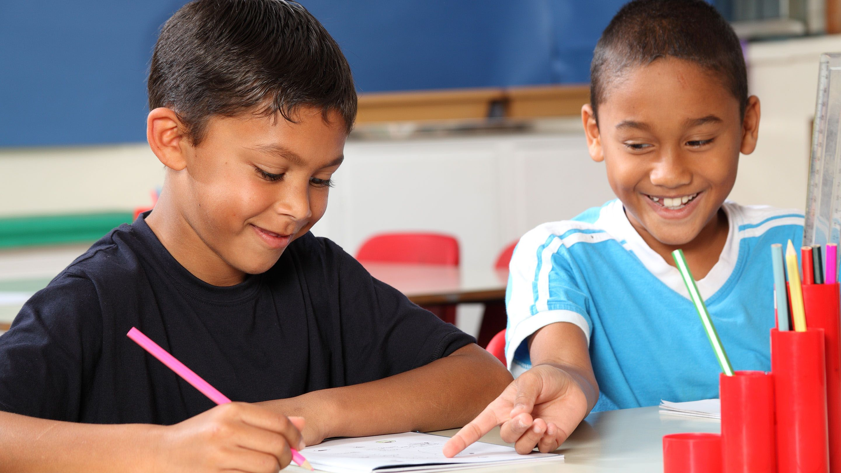 Two elementary school boys sit together, writing and laughing.