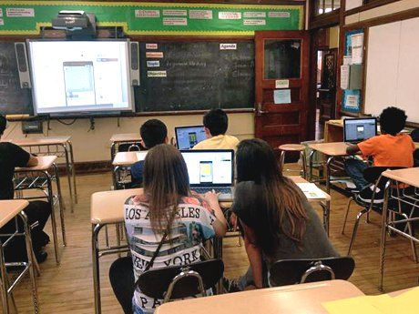 Students in class working in pairs on laptops looking at a projection on screen