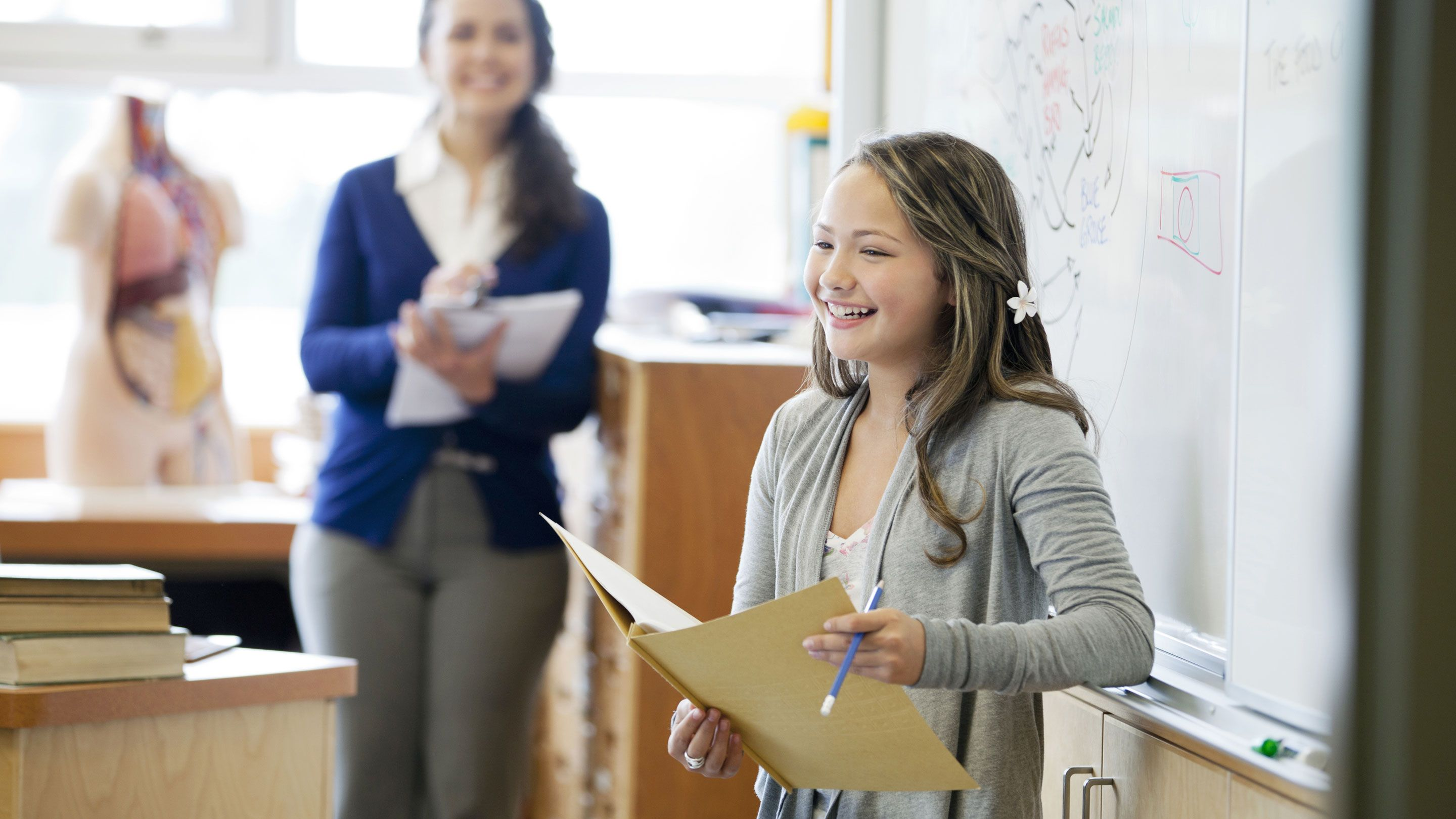 A student confidently speaks to her class as her teacher smiles in the background.