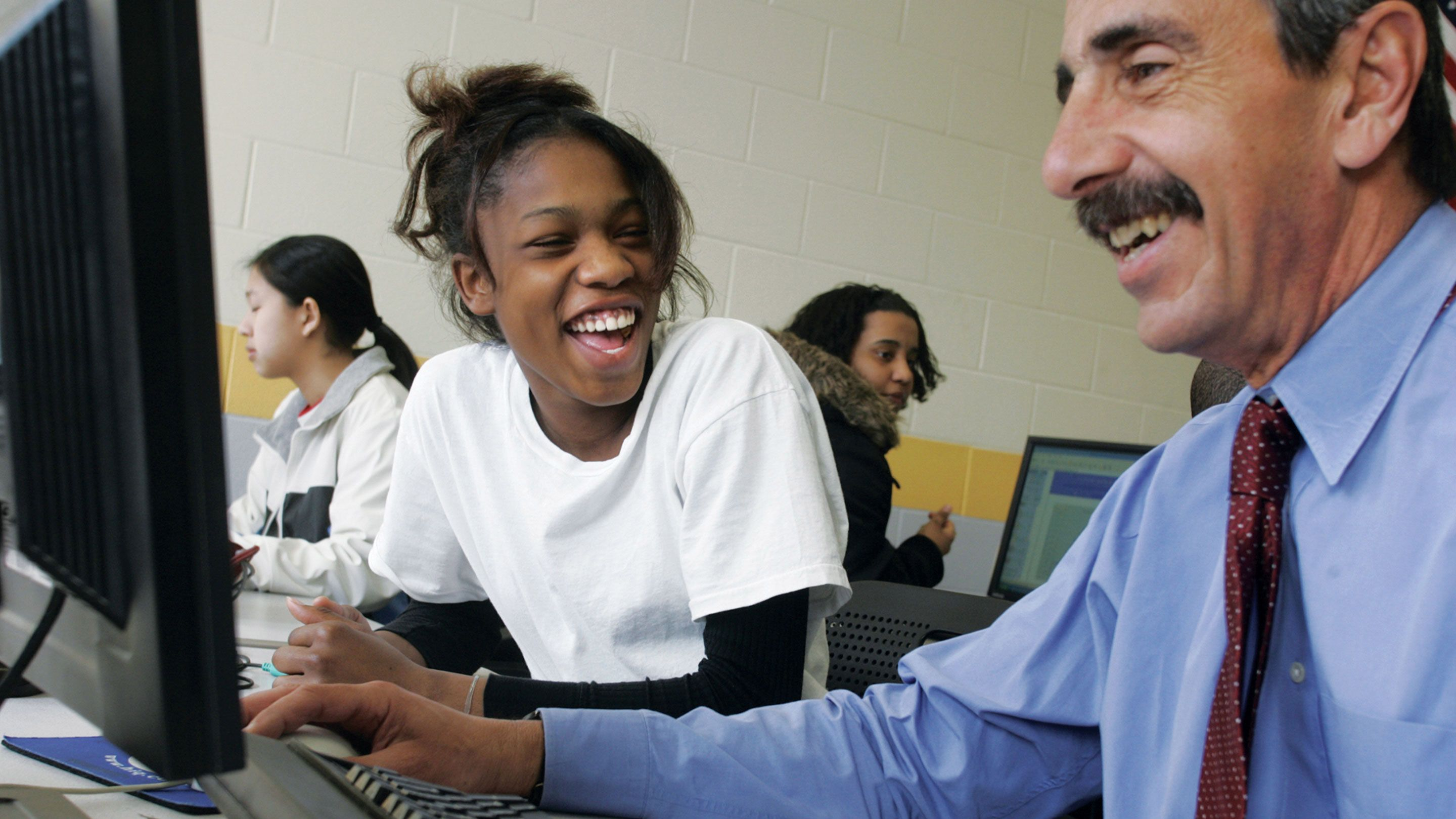 A teacher and student laugh while working at a computer together.