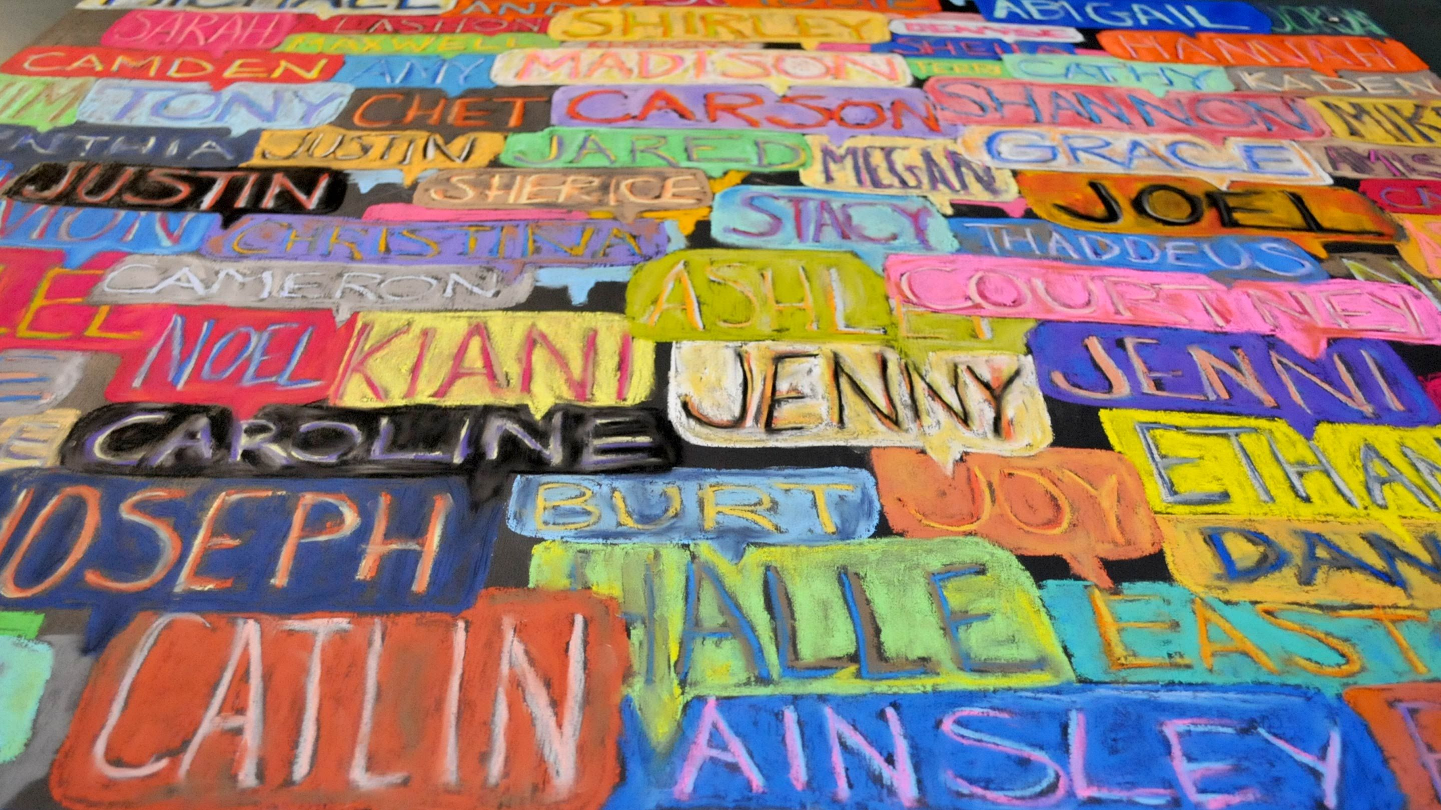 A chalkboard covered with student names in bright colors.