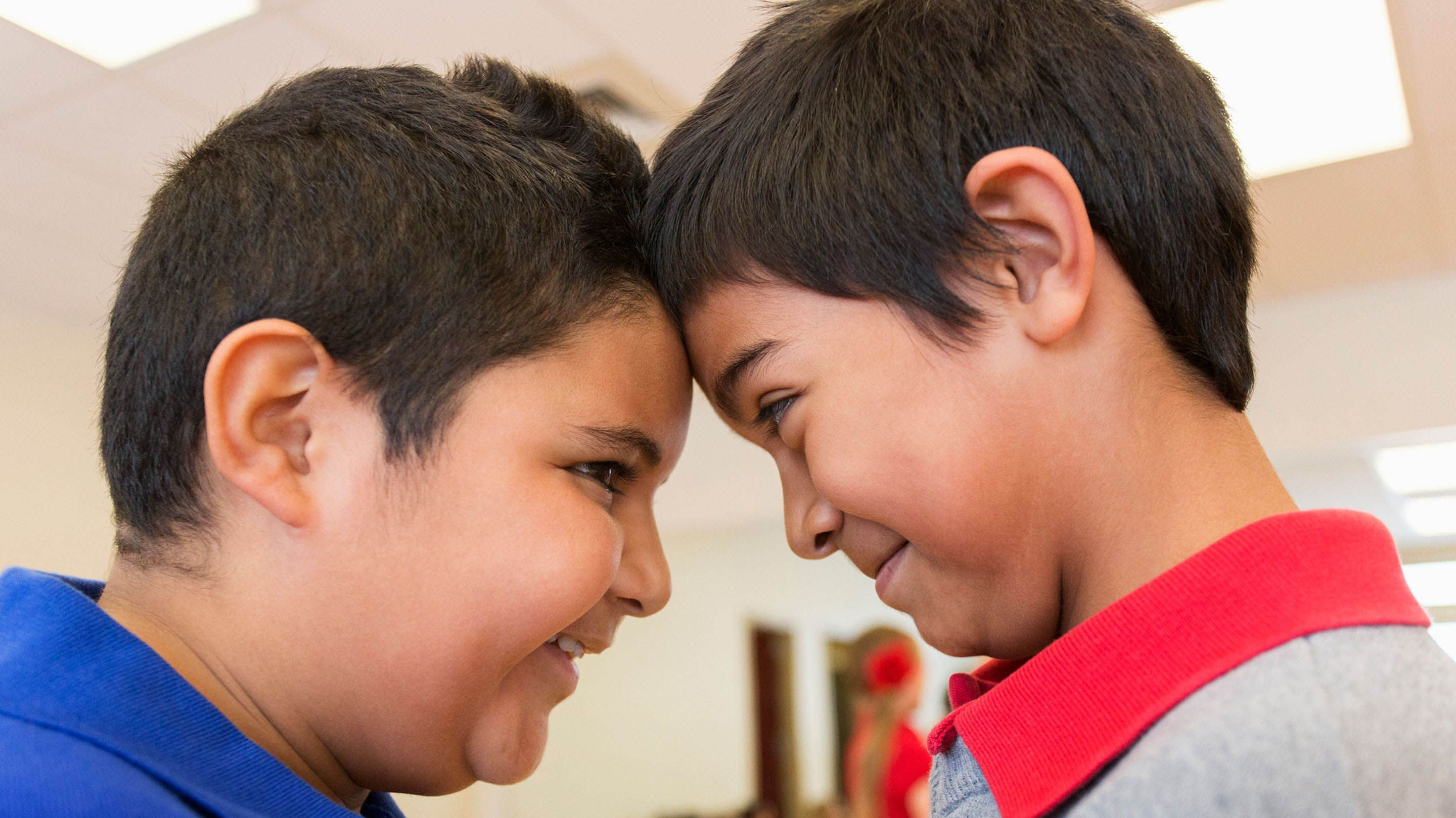Two boys look into each other's eyes, a technique that builds empathy.