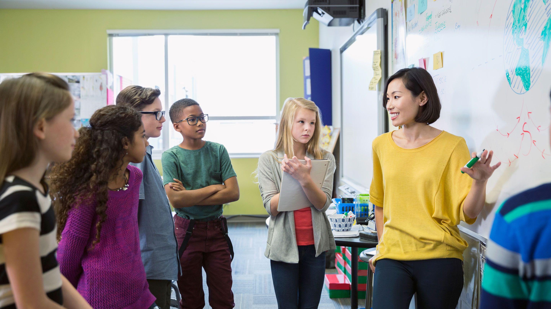 A teacher confidently explains a concept to students.