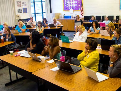 A classroom full of teachers listening with laptops open