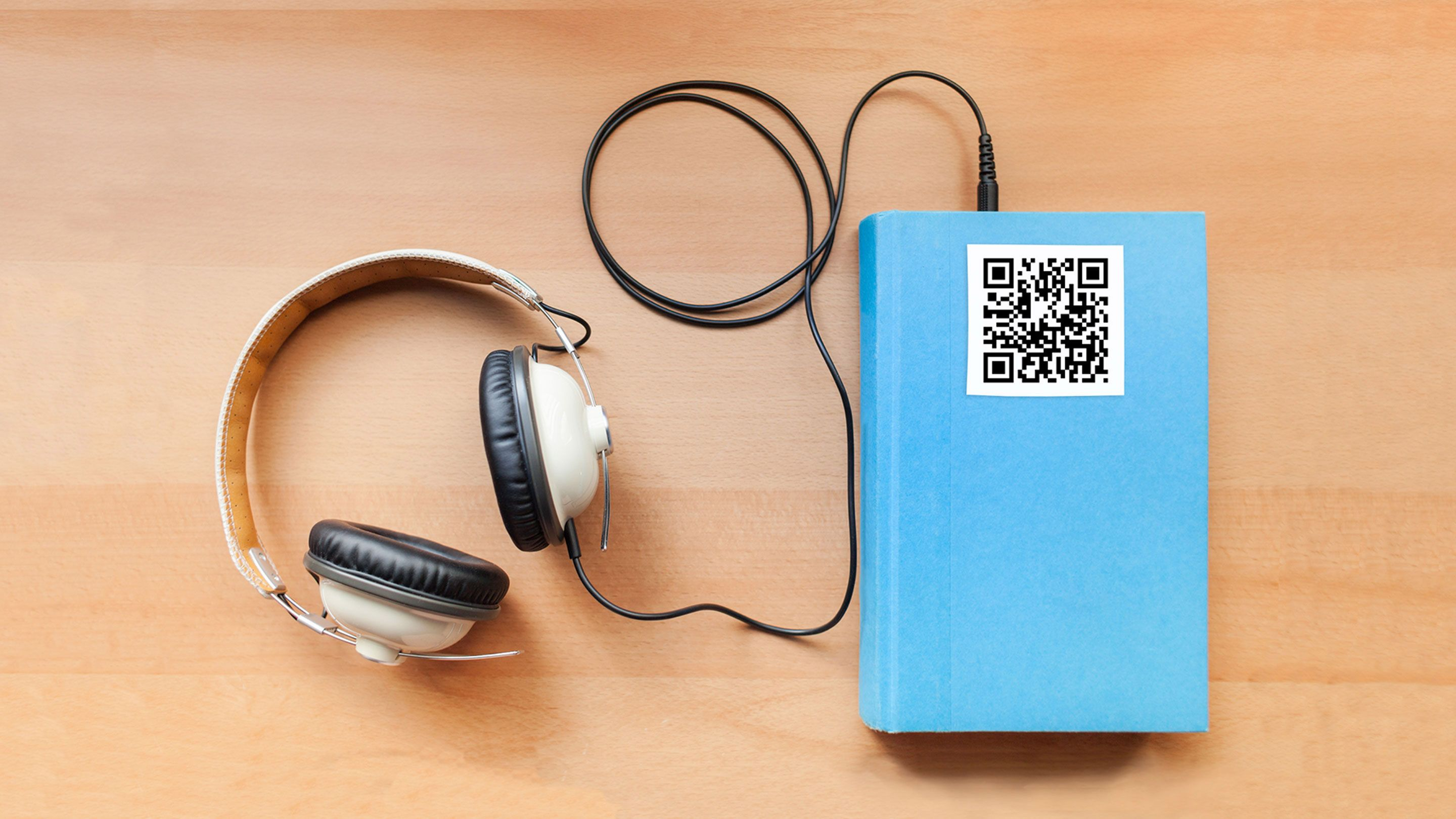 Image of a book with a pair of headphones attached