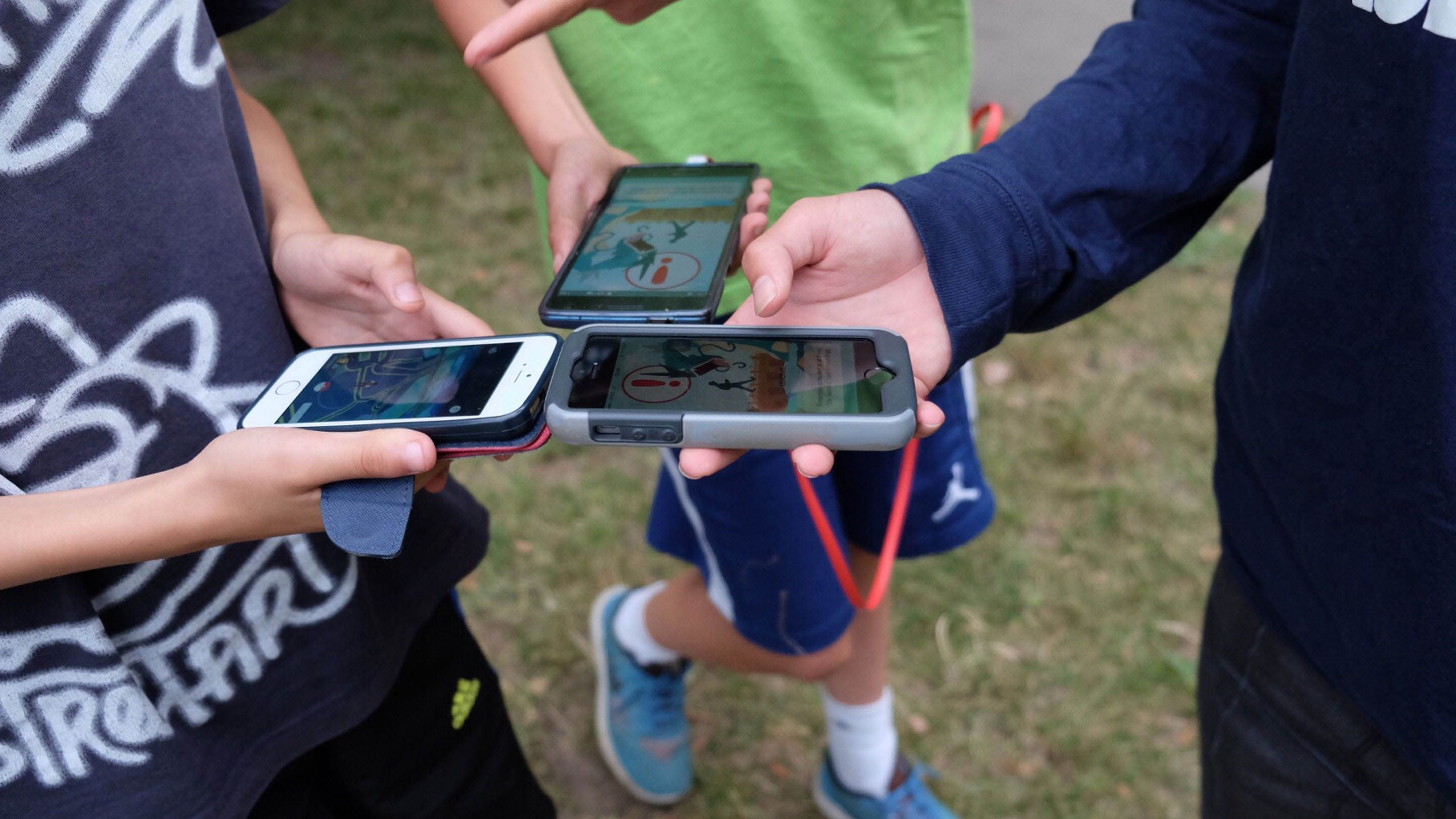 Three students are standing on the grass, a close up on their arms extended, smartphones in their hands, and Pokemon Go on their screens.