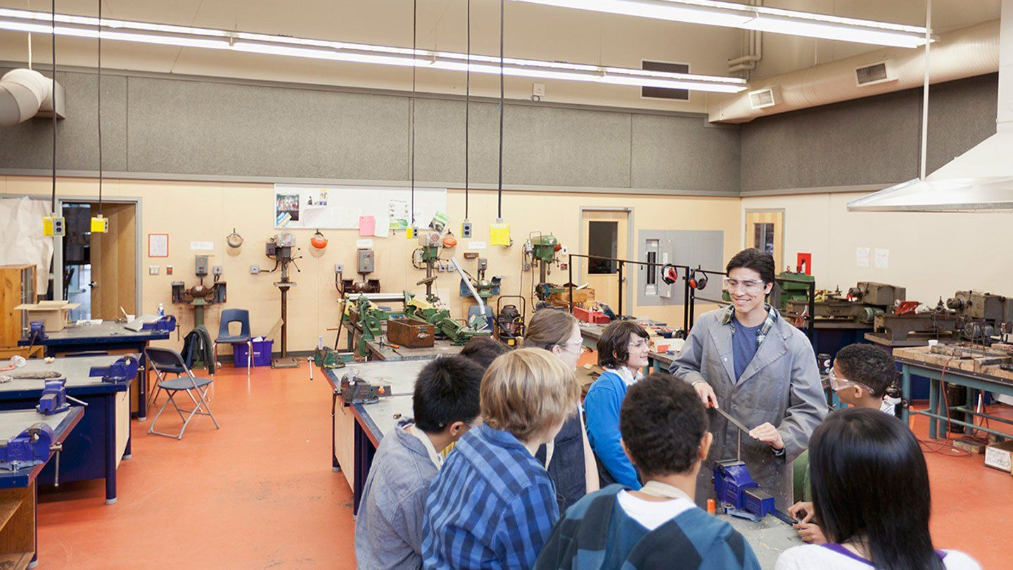 A male teacher wearing goggles and a long jacket in a large science laboratory is surrounded by a group of eight students, all looking up at him, also wearing protective goggles.