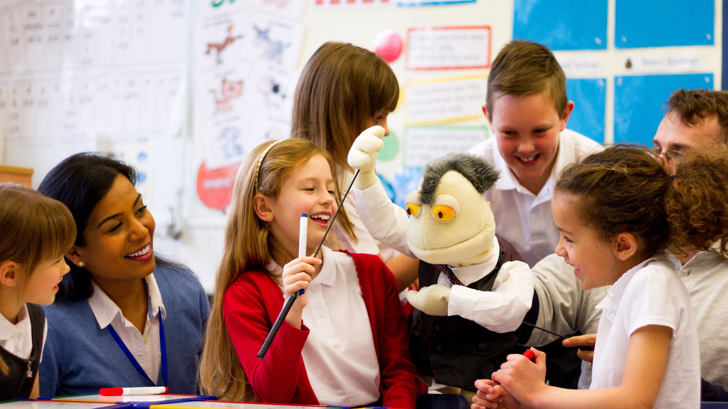 photo of students and teachers playing with a puppet
