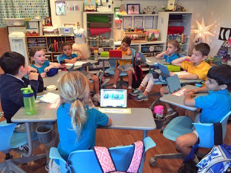 Group of eight elementary school children sitting in circle at desks, some with tablets
