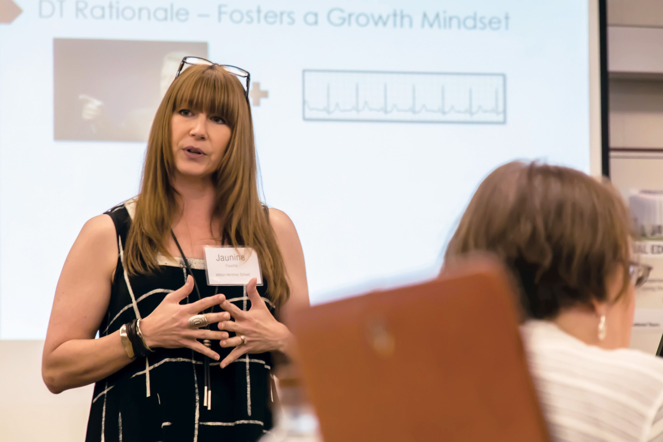 Woman standing in front of screen presenting to other teachers.