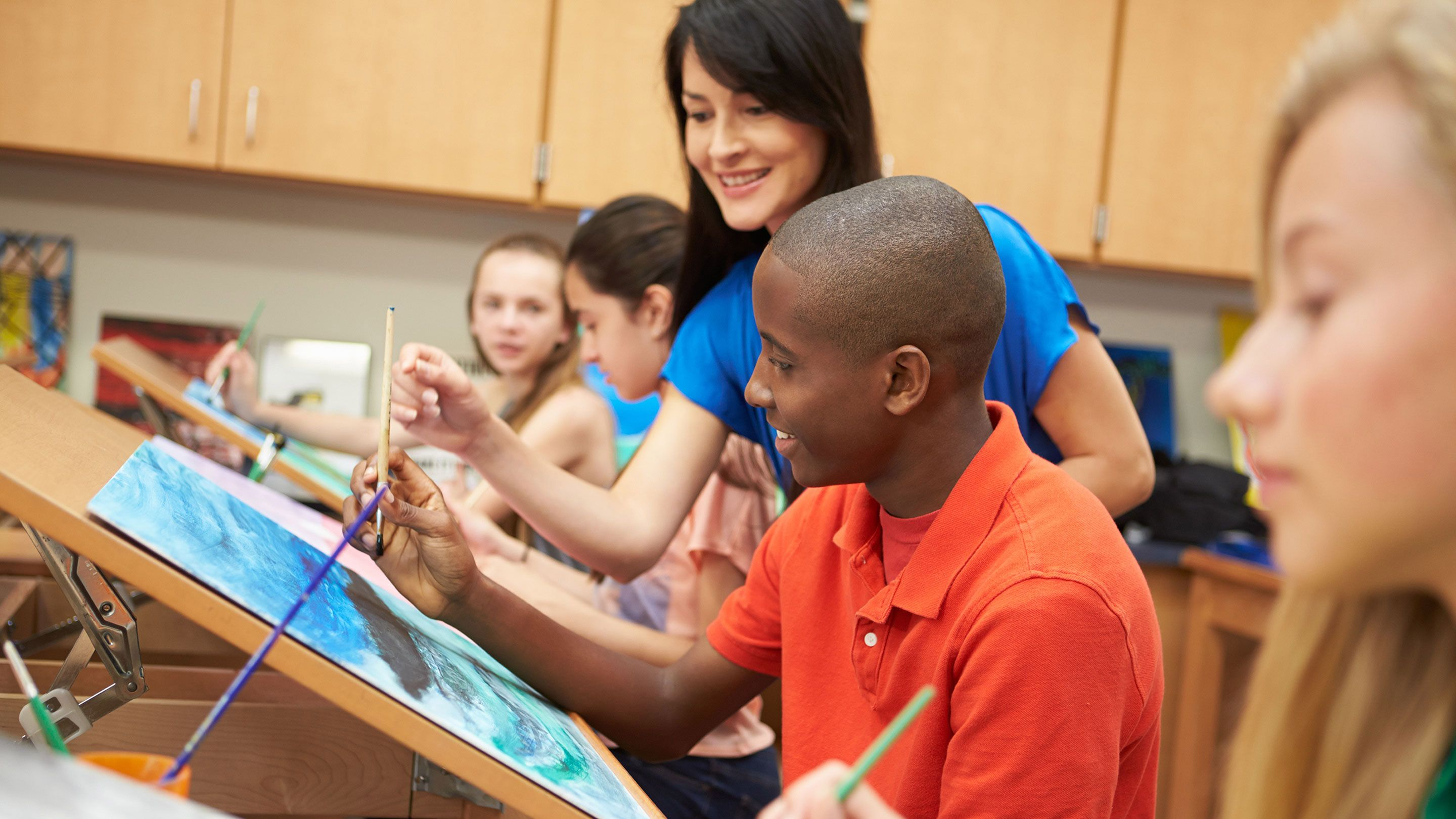 A teacher guides several high school aged students as they sit at easels, painting.