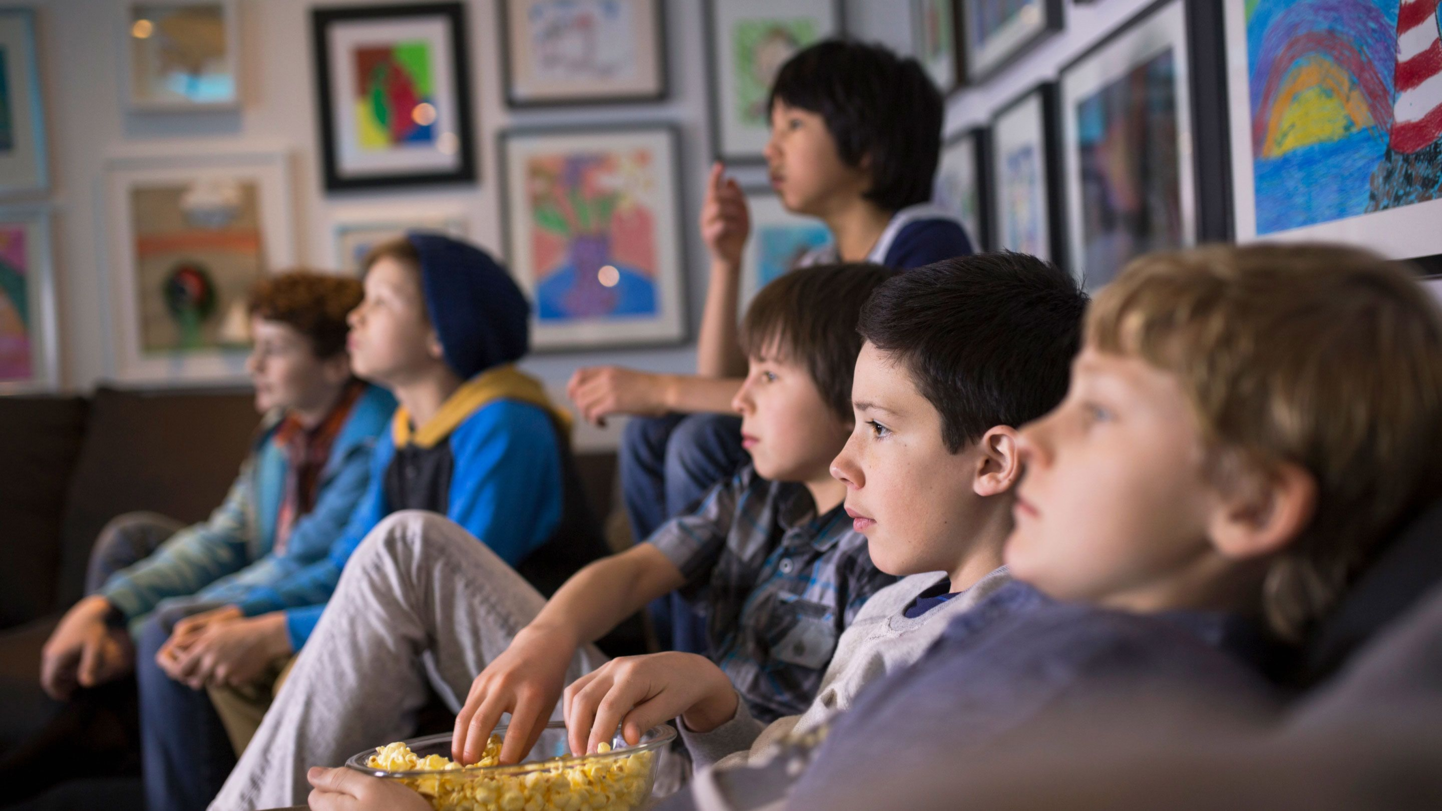 Six preteen boys are sitting on brown couches, eating popcorn, and watching a movie.