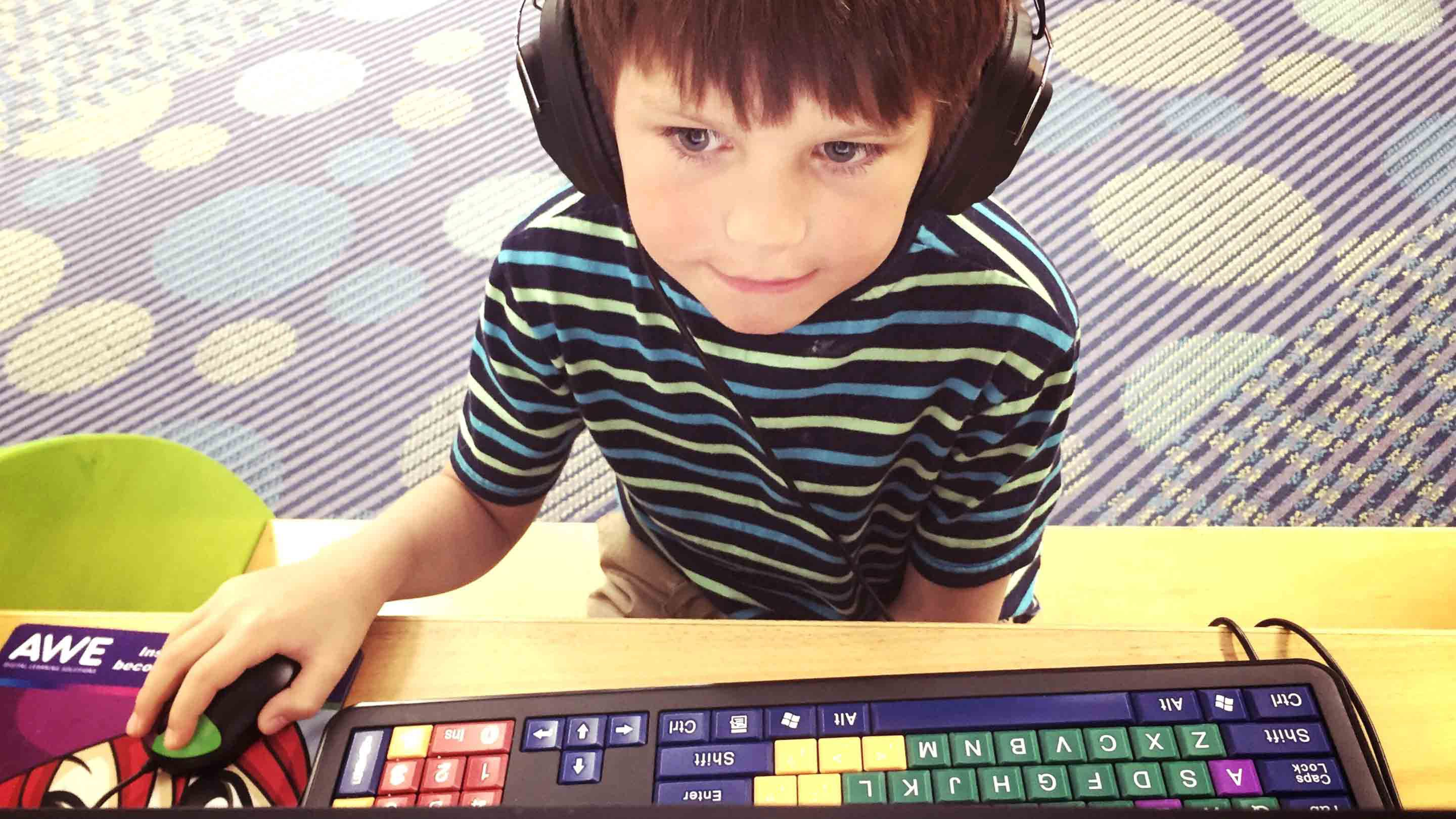 A boy wearing headphones works at a computer.
