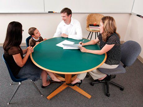 Young boy sitting between and woman and man at a round table with a teacher sitting across from them holding papers