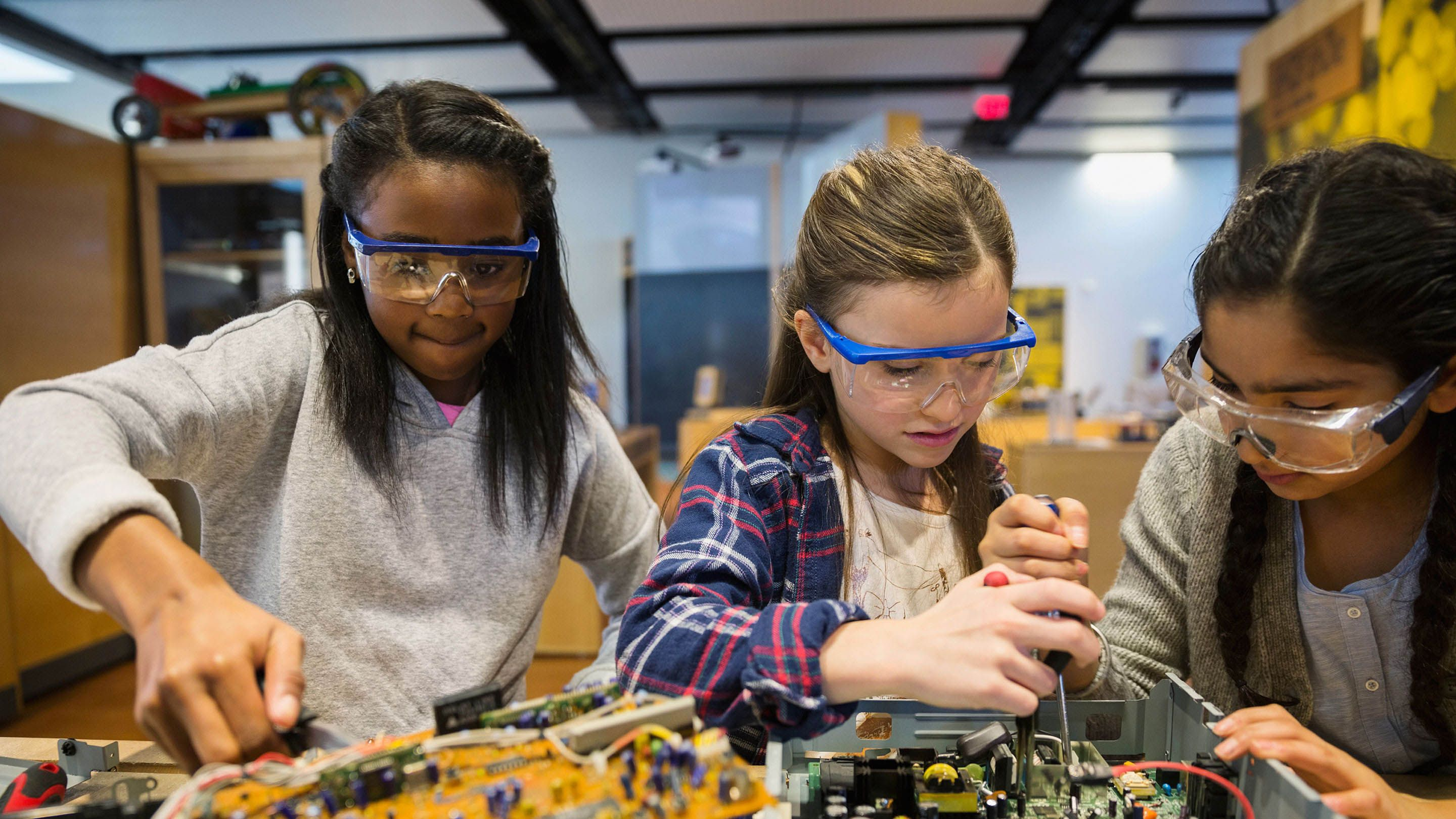 Three girls work on computer circuitry.