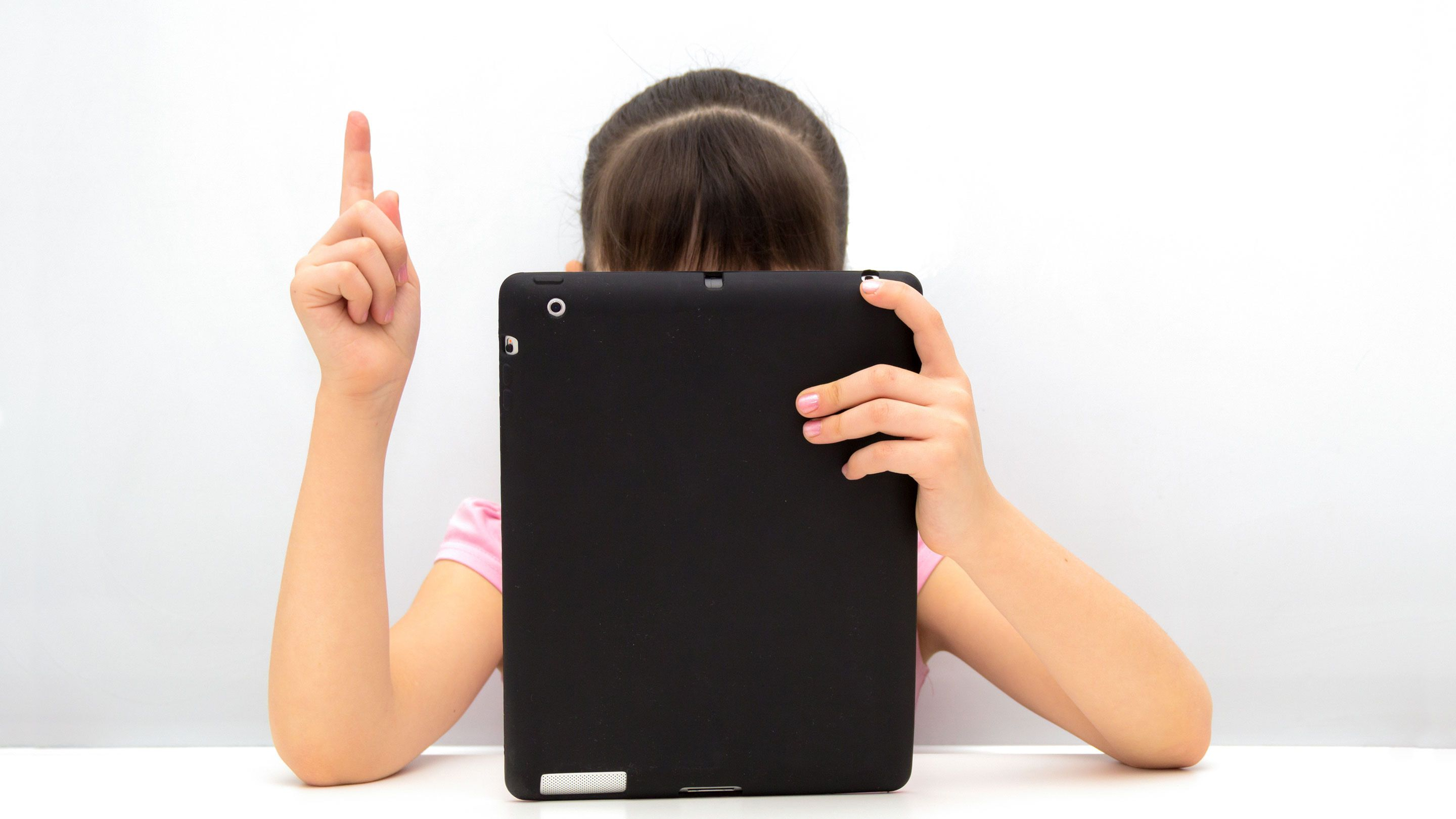 A girl hidden behind a tablet computer raises her hand.