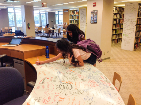 A photo of 2 female students writing a whiteboard table with colored markers.