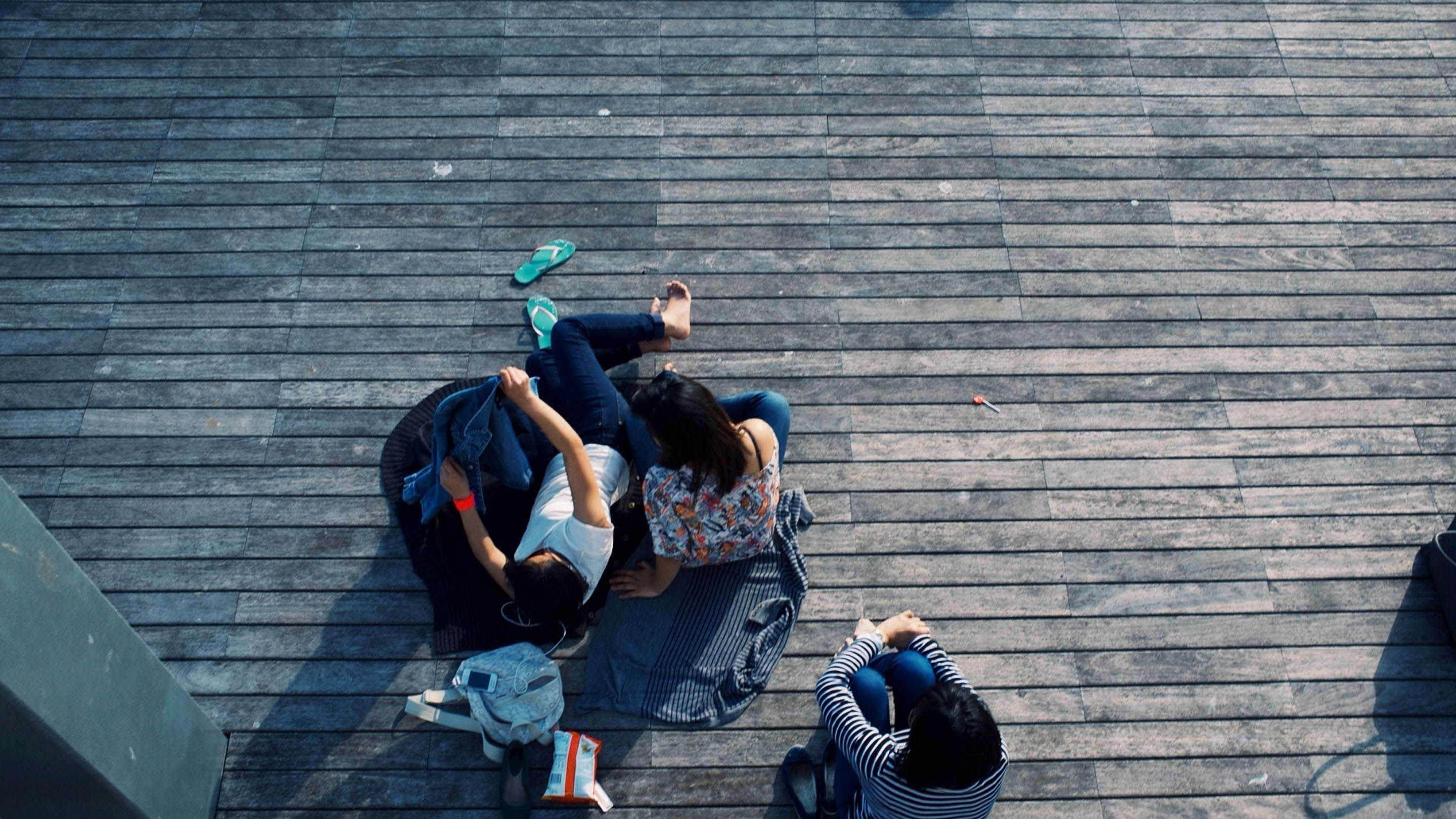 photo of a birds-eye-view of people sitting on a deck