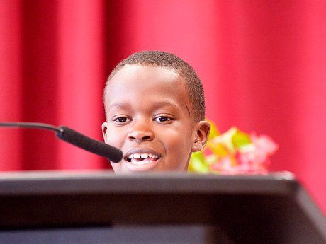 Young boy speaking, almost hidden by the podium he's standing behind