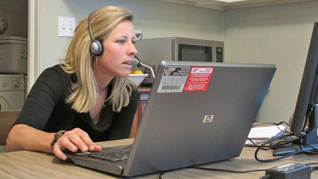 Woman wearing a headset sitting at her kitchen table with her laptop