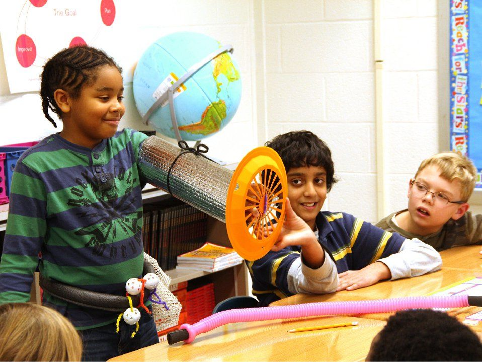 Boy showing his project to classmates -- a silver tube over his arm with a globe tied to the top and a fan at the end of the tube
