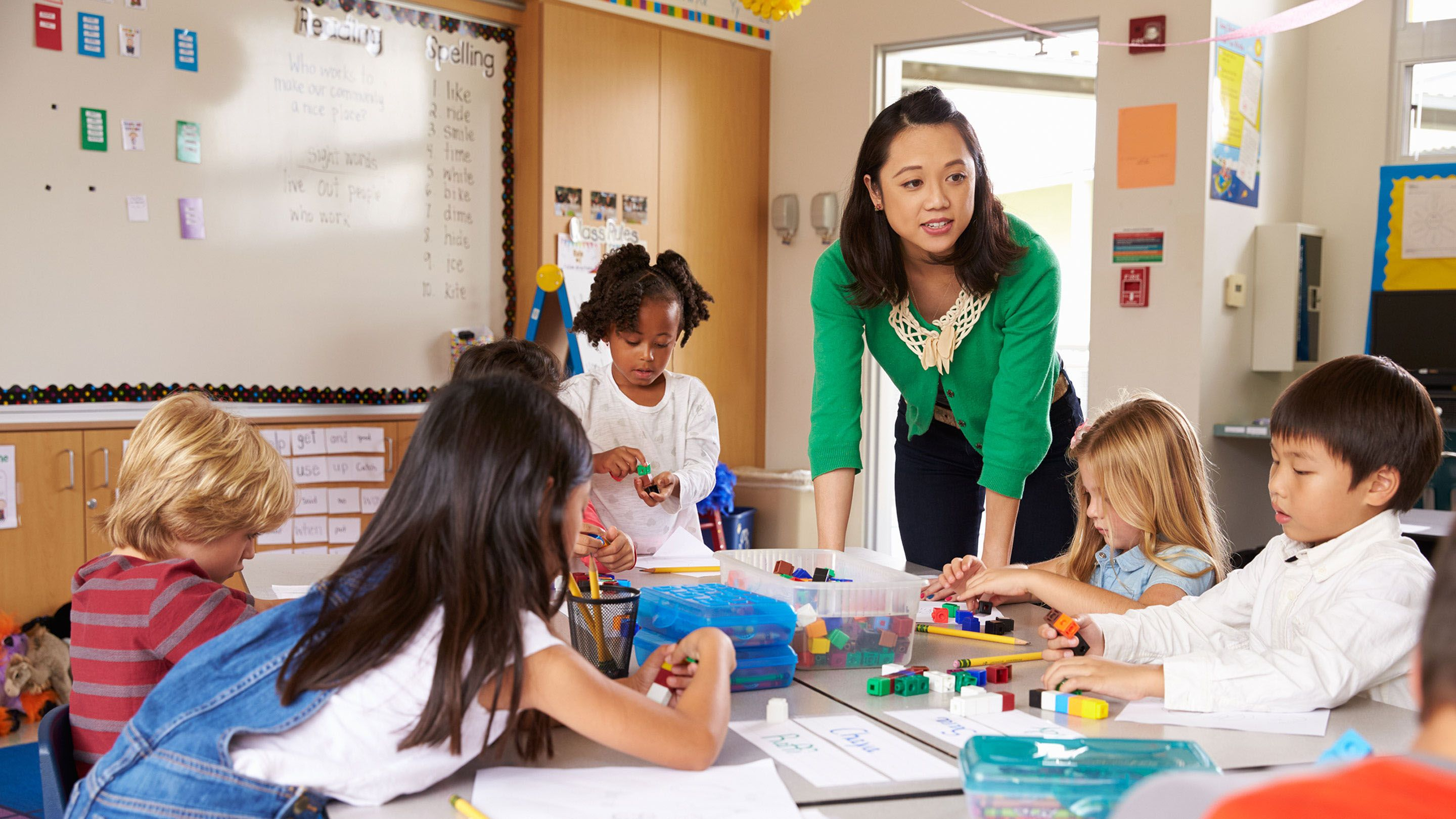An elementary grade level teacher stands at a table giving instruction while young children are writing.