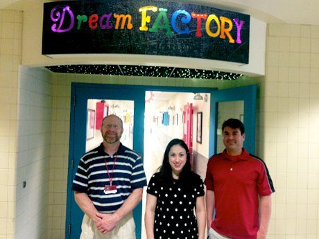"Three adults are standing outside of the doors of a school hallway, below a sign that says, ""Dream Factory."""