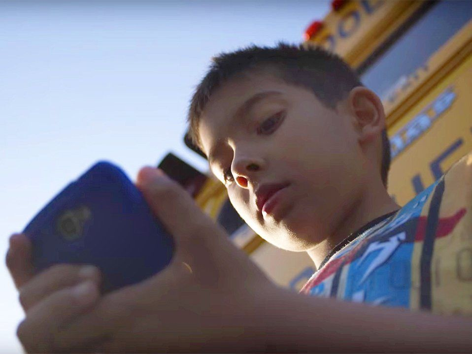 A child looks at a cell phone.