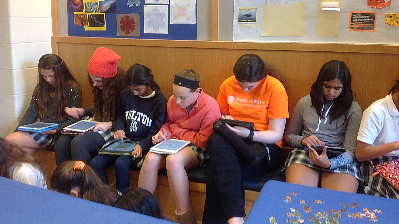 Girls play a math game on their iPads.